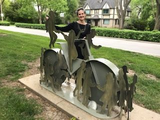 Lincoln artist Liz Shea-McCoy stands by sculpture of bicycle