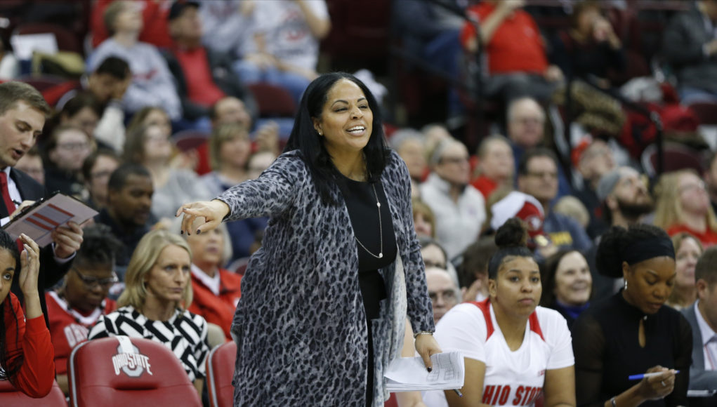 Ohio State women's basketball assistant coach Carrie Banks in front of the bench in a game versus Michigan (courtesy UNO athletics)