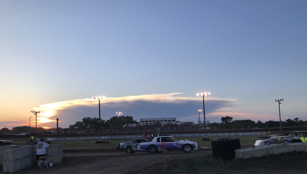 dirt track with fans and sunset in background