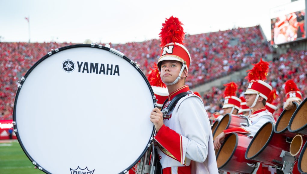 A bass drummer from the Cornhusker Marching Band gets ready to take the field during pregame