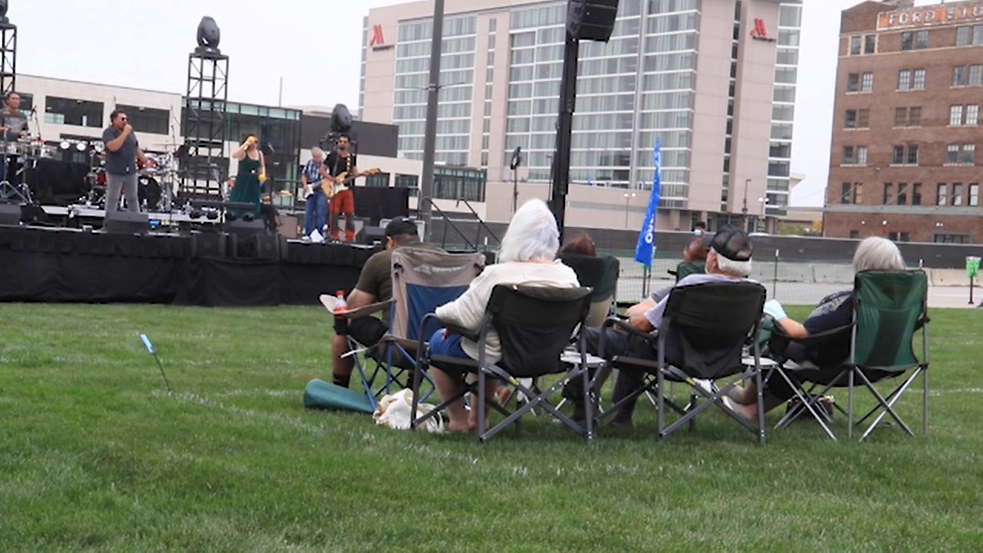Six people in lawn chairs watch a band play on an outdoor stange