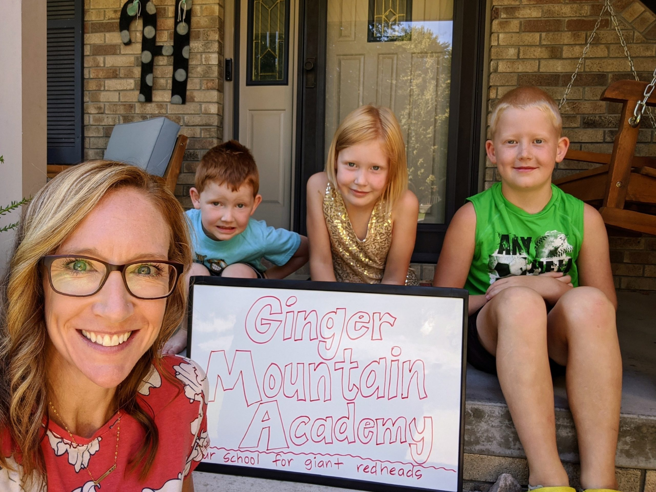 Image of a homeschool mom with three children on their first day of school surrounding a sign that says