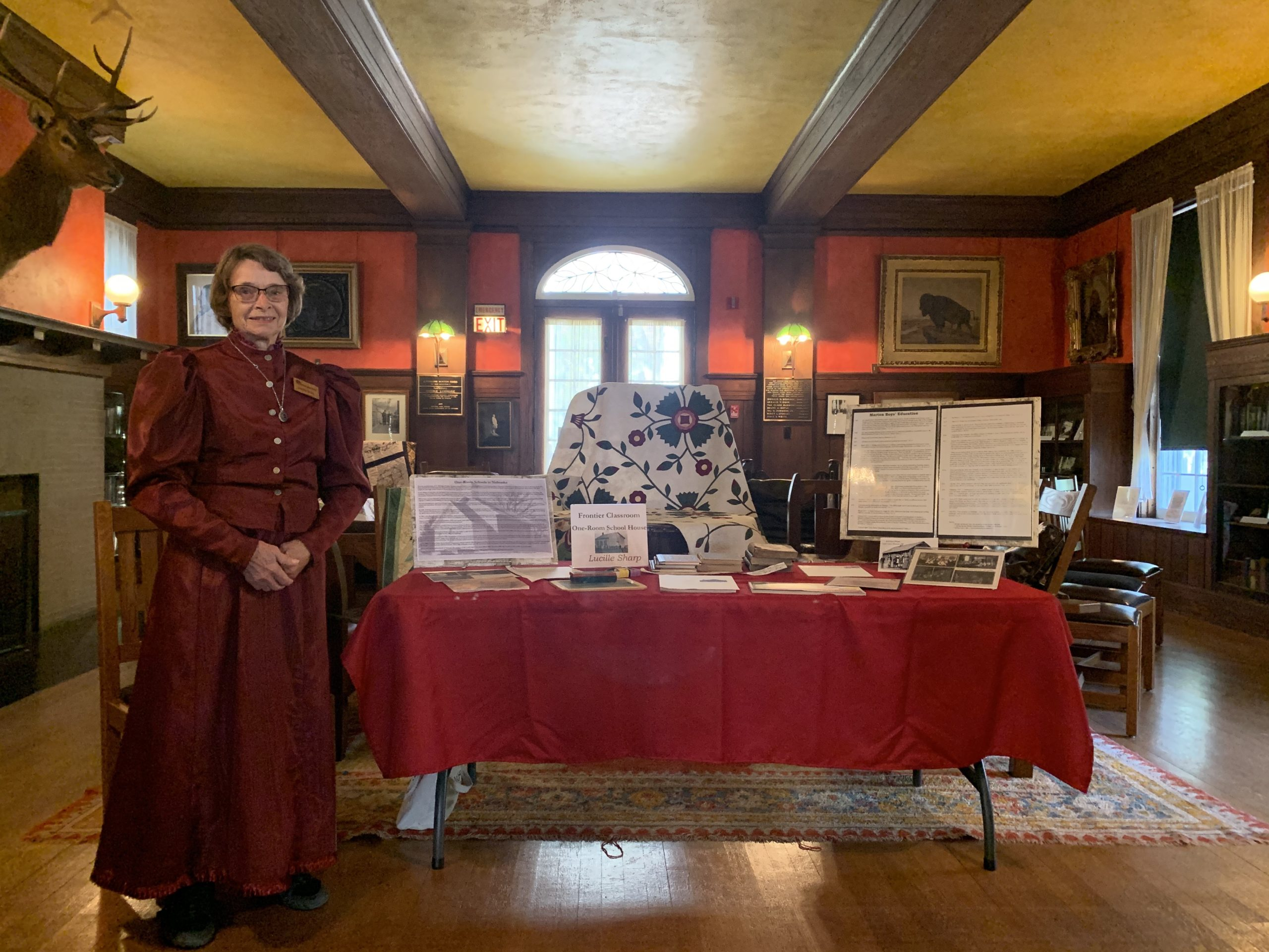 Lucille Sharp poses in a red, pioneer era dress near next to her display on one-room schoolhouses in the Arbor Lodge Mansion