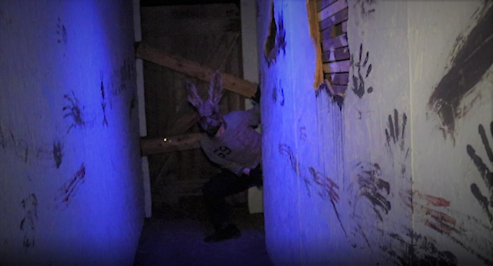 A masked man peeks from behind a wall in a haunted house