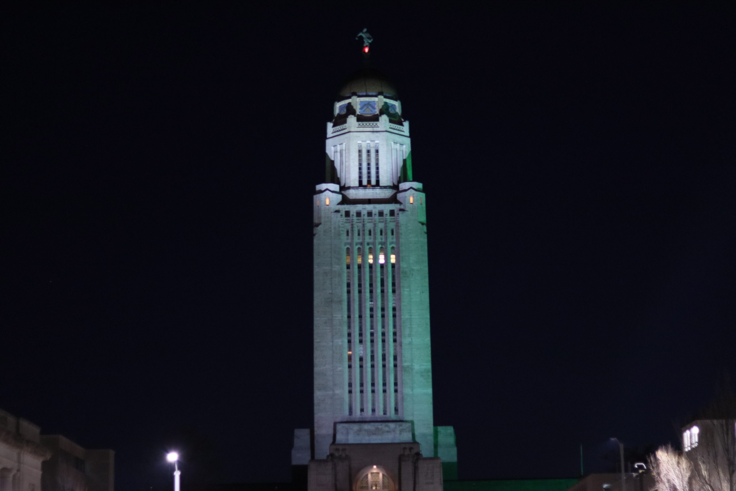 The Nebraska State Capitol glows green at night in support of Veteran's Day.