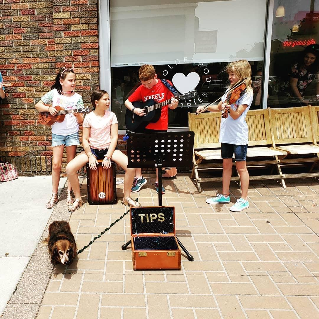Four of Blue Raven Music Studios students perform outside of Goldenrod Pastries in College View.