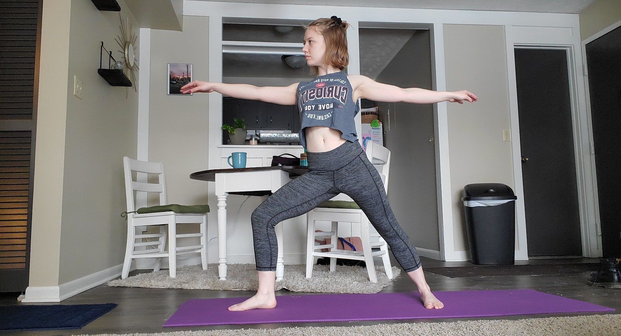 Woman staring forward doing yoga pose on purple yoga mat in her living room