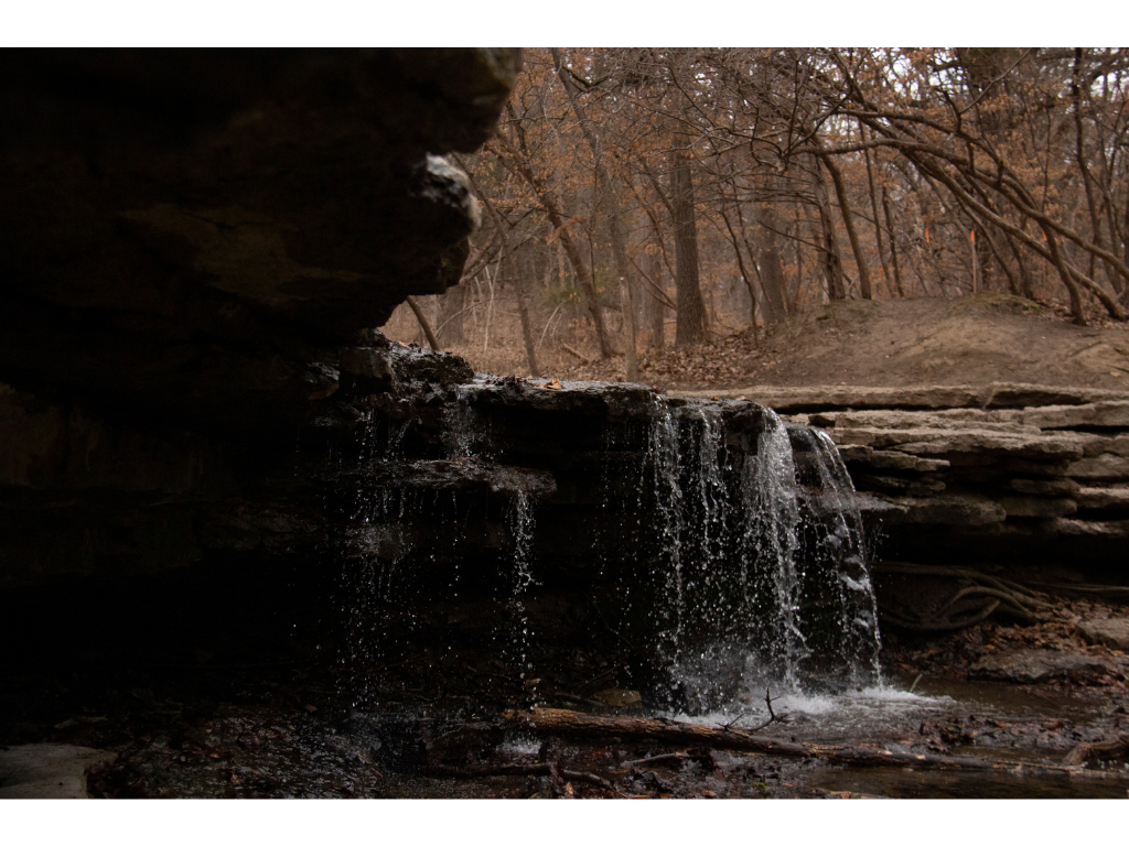 A small waterfall of Stone Creek is shown from underneath the rockface.