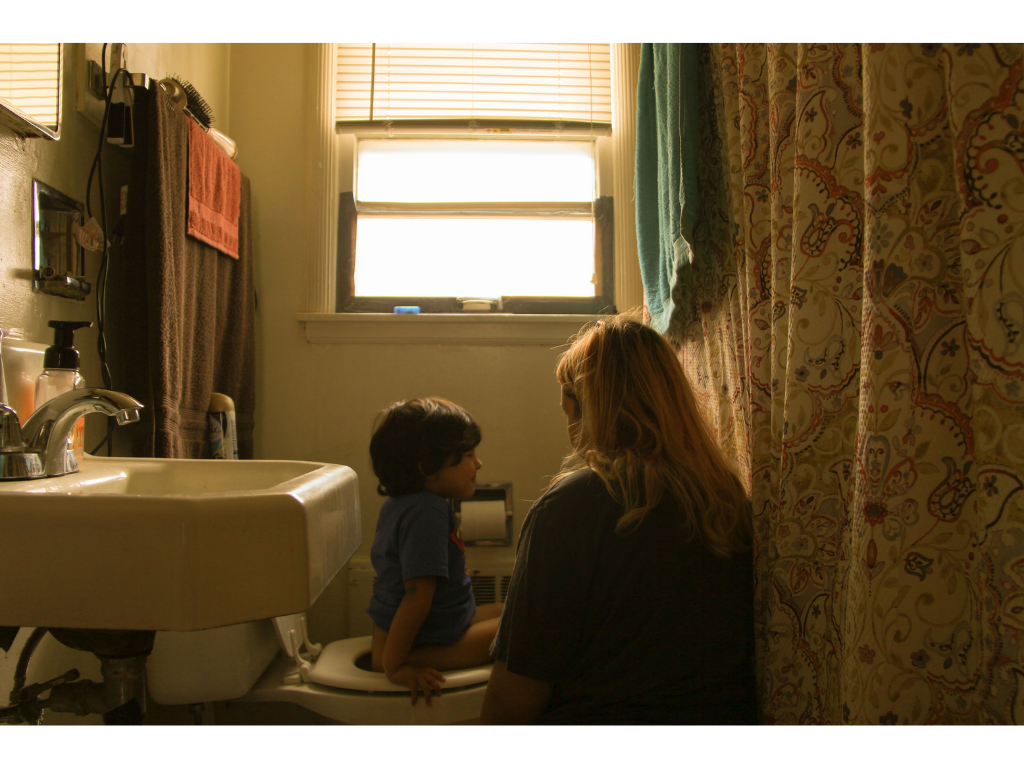 Sam Vargas and her young son in their home bathroom.