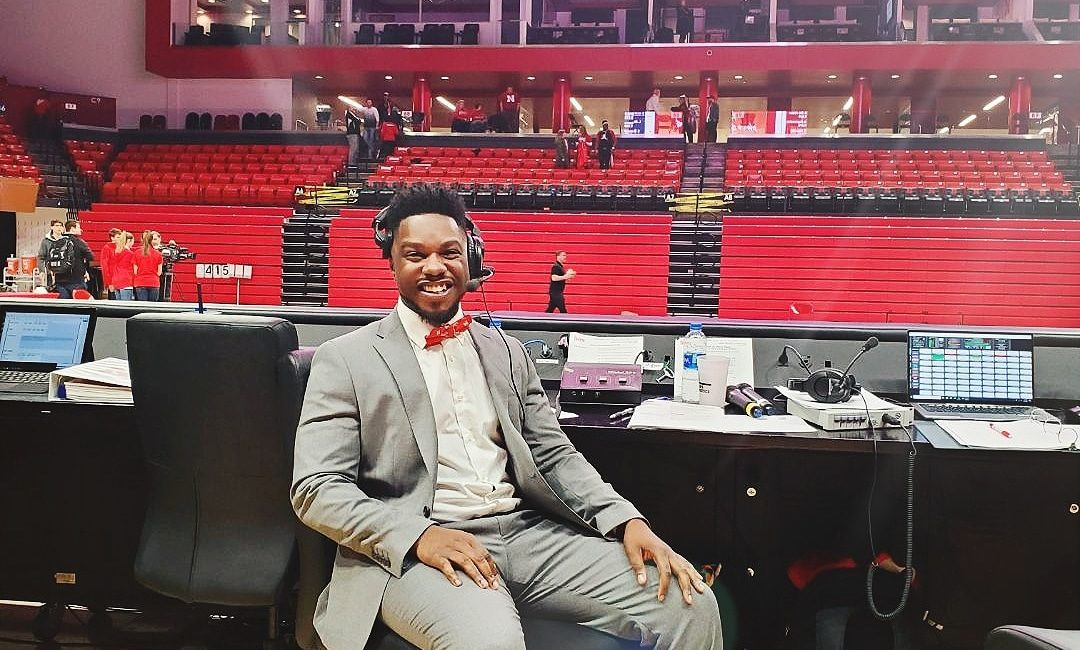 DeWayne Taylor sits in a chair in front of a sporting event