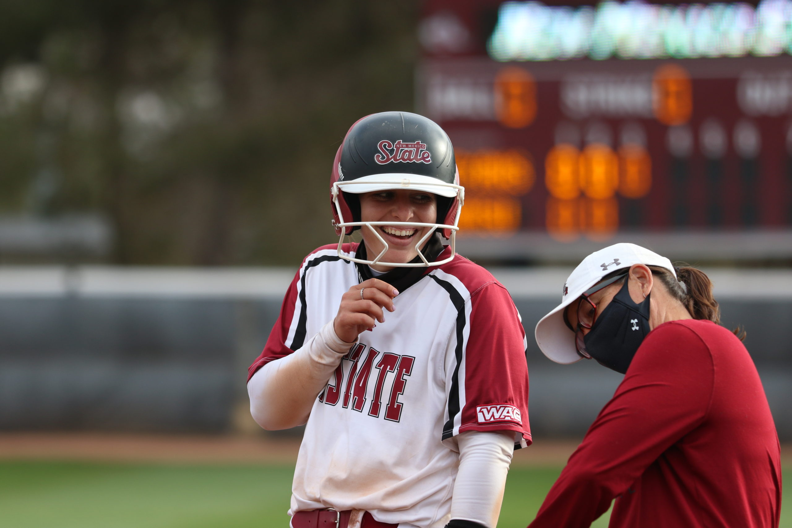 NM State senior catcher Nikki Butler smiles at her first base coach after a base hit against Tarleton State on Apr. 16 in Las Cruces, N.M.