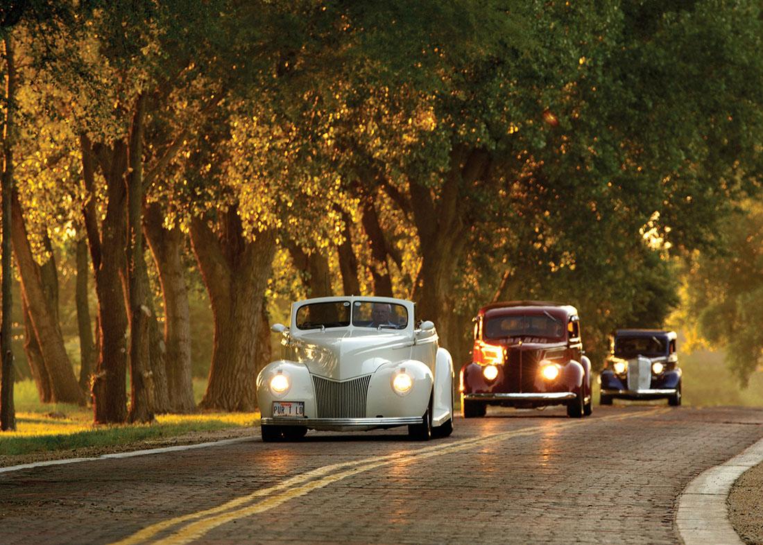 Automobiles travel across a brick highway.