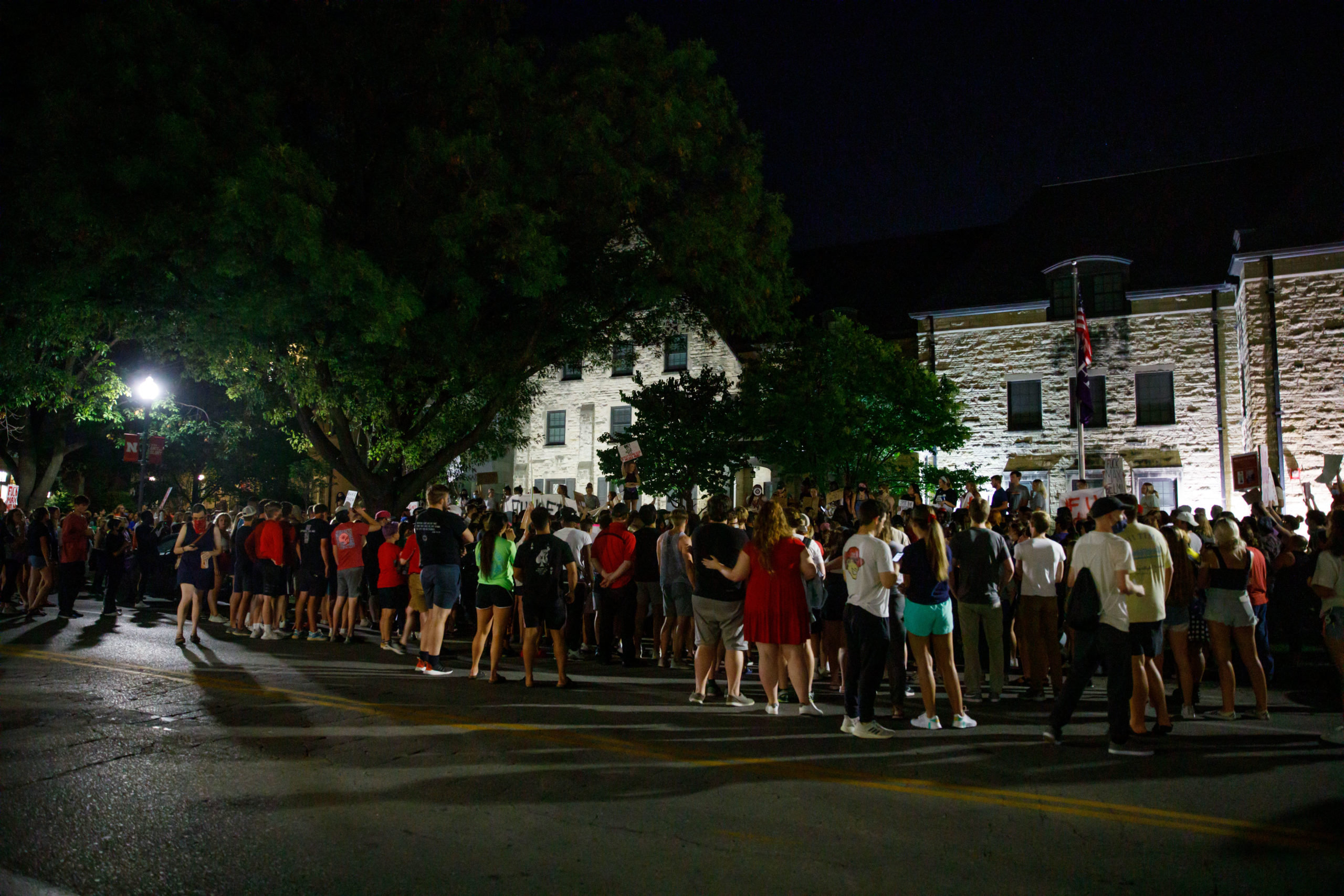 UNL students stand outside of fraternity house