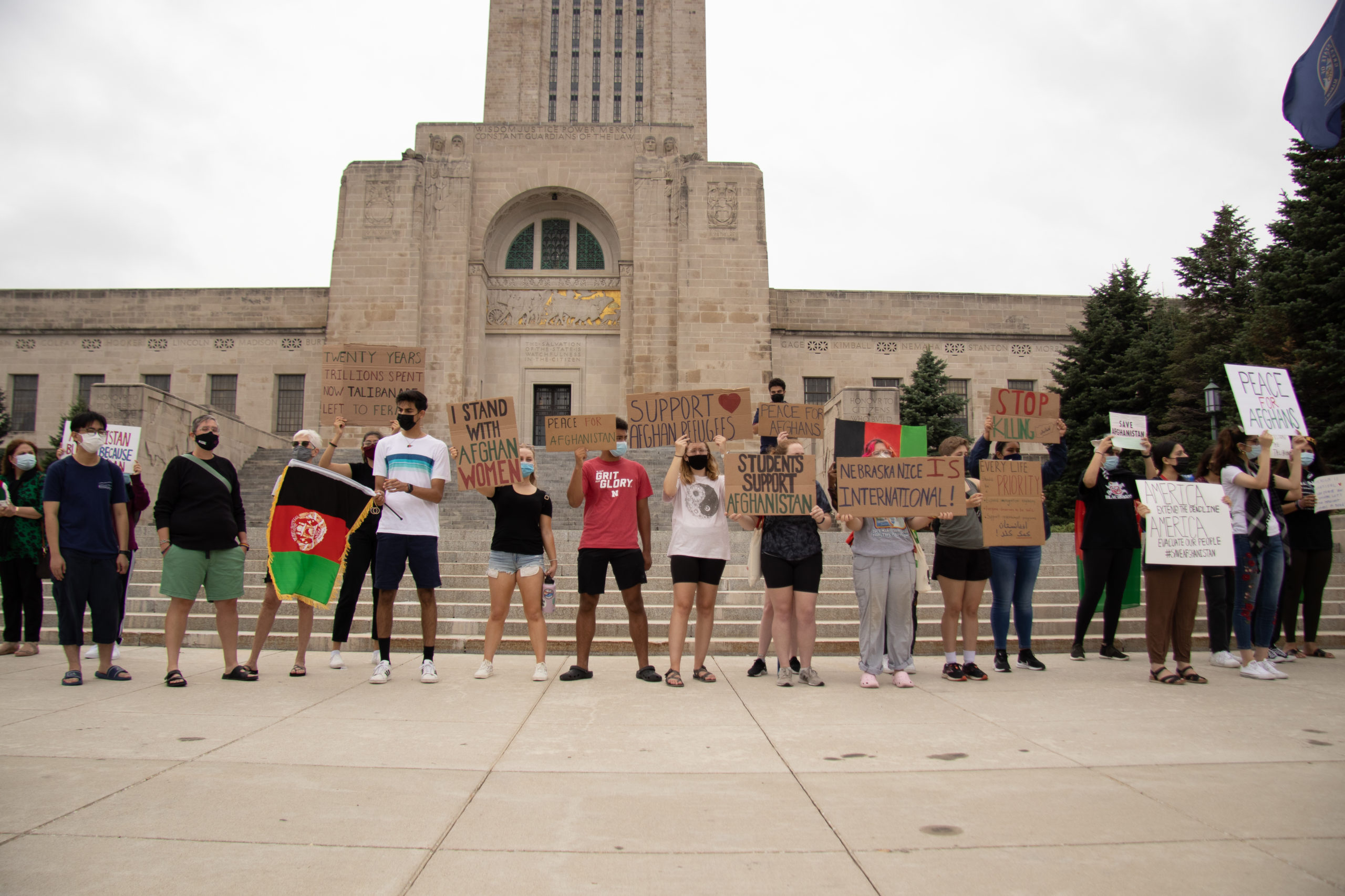 Rally participants stand in front of the Nebraska State Capitol holding up handmade signs facing the road.