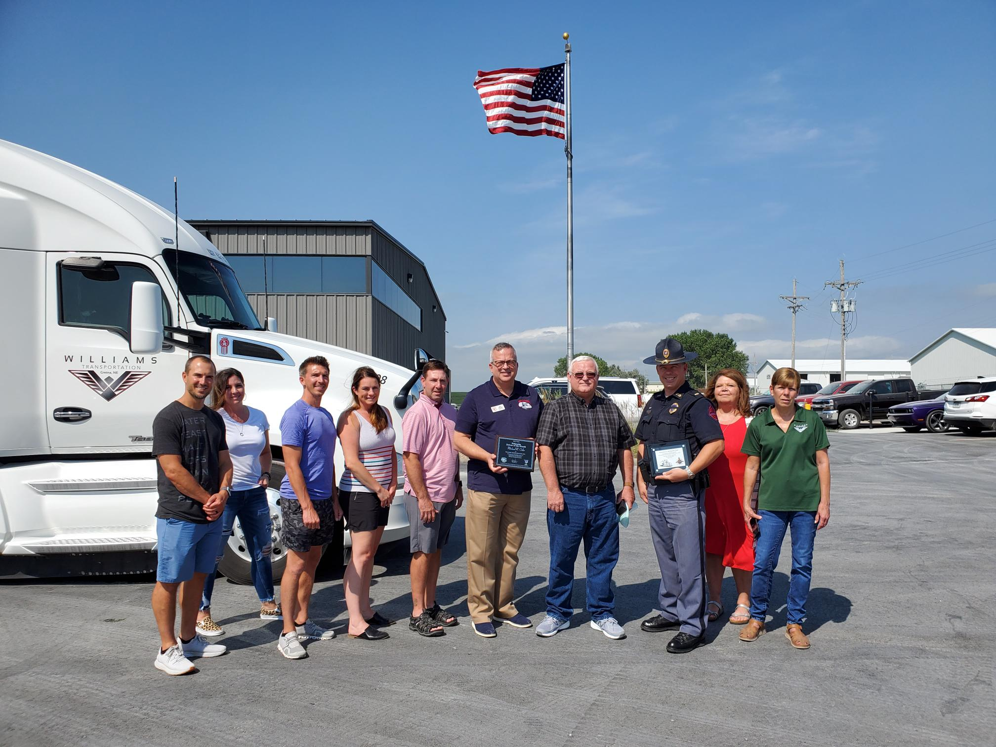 A group of truckers pose for a photo in front of a truck