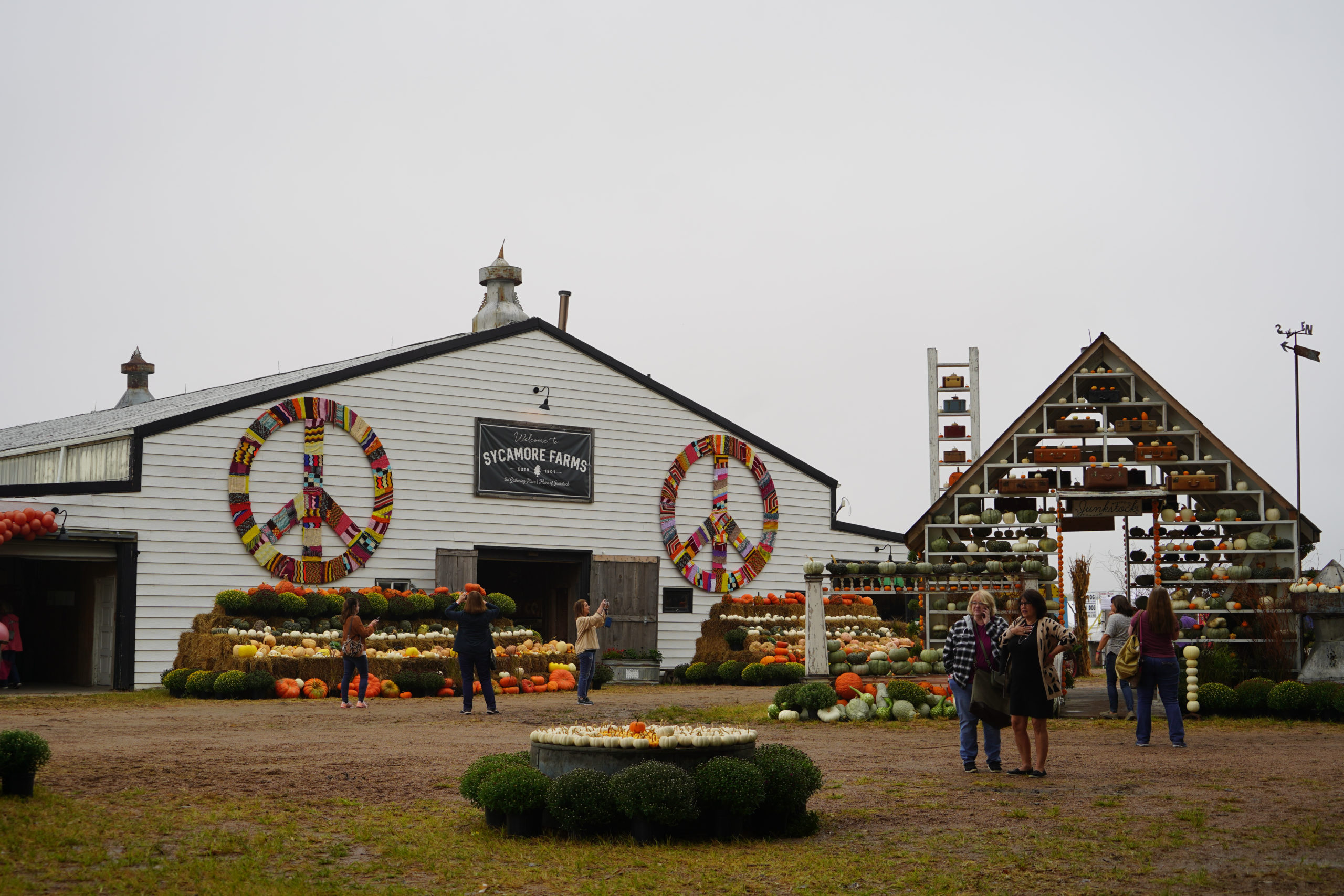 The barn at Sycamore Farms is decorated with pumpkins, a hut, and flowers.