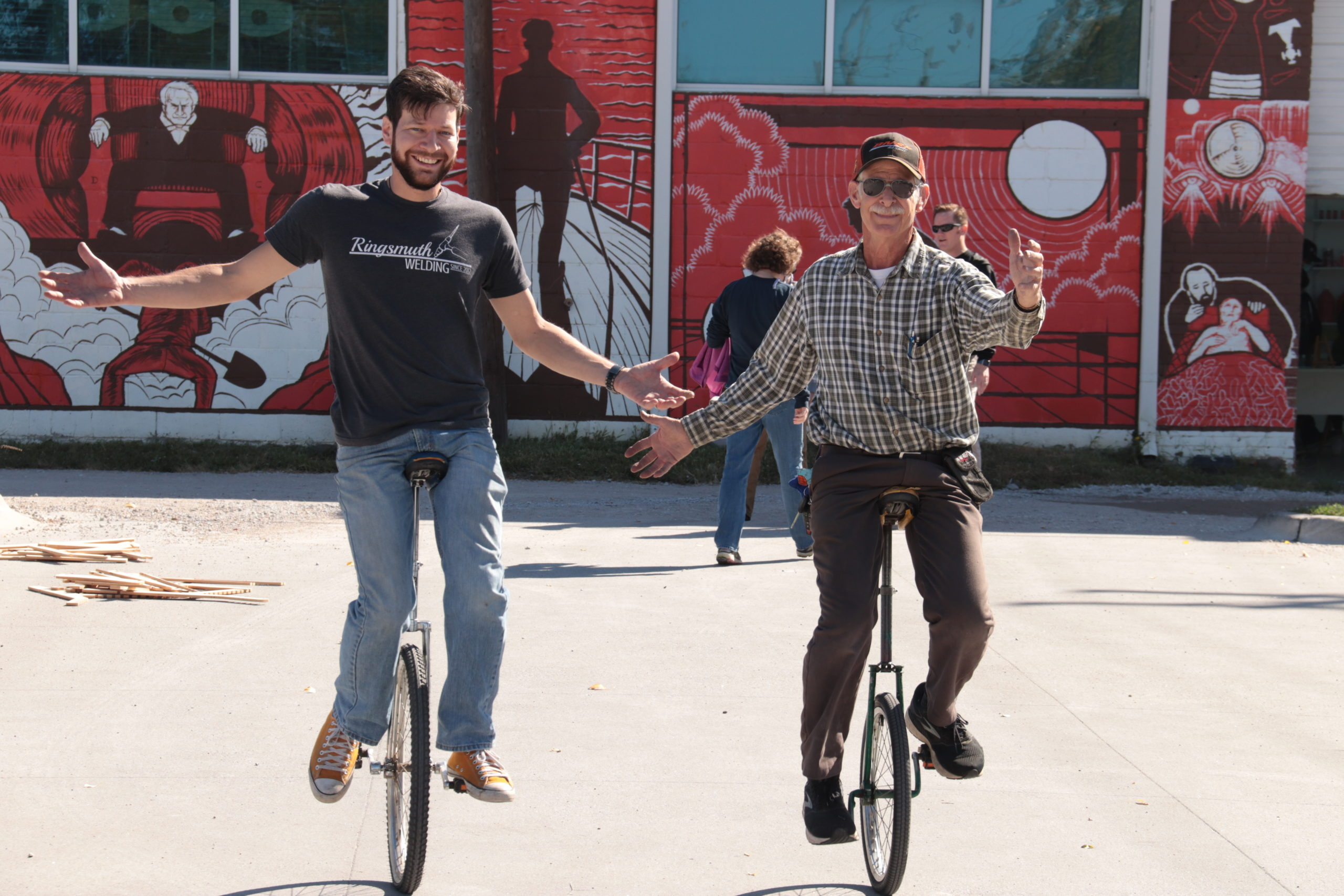two men riding unicycles